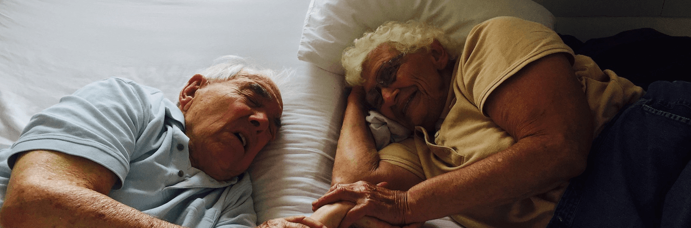 elderly couple laying down together