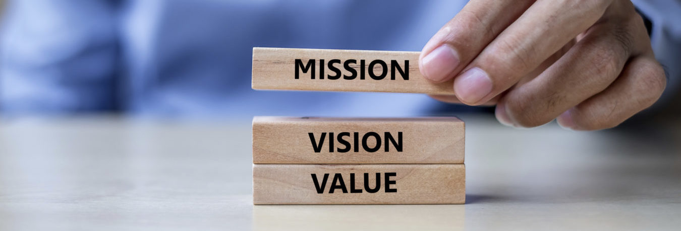 A Man placing block titled Mission above Vision and Value Blocks